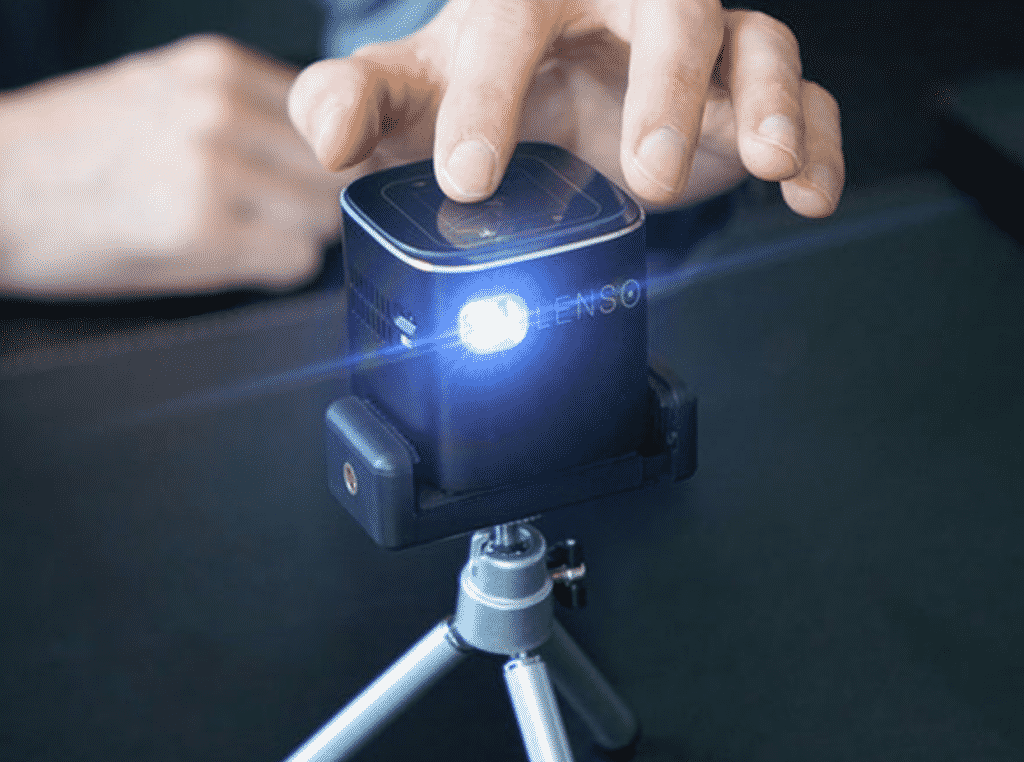 Lenso Cube 1080P pocket projector with a human hand.
