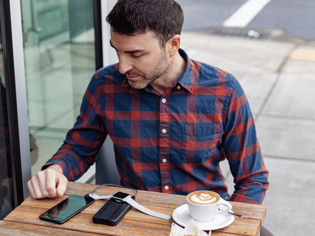 A man with a coffee using the BatteryPro portable charger for iPhone and Apple Watch