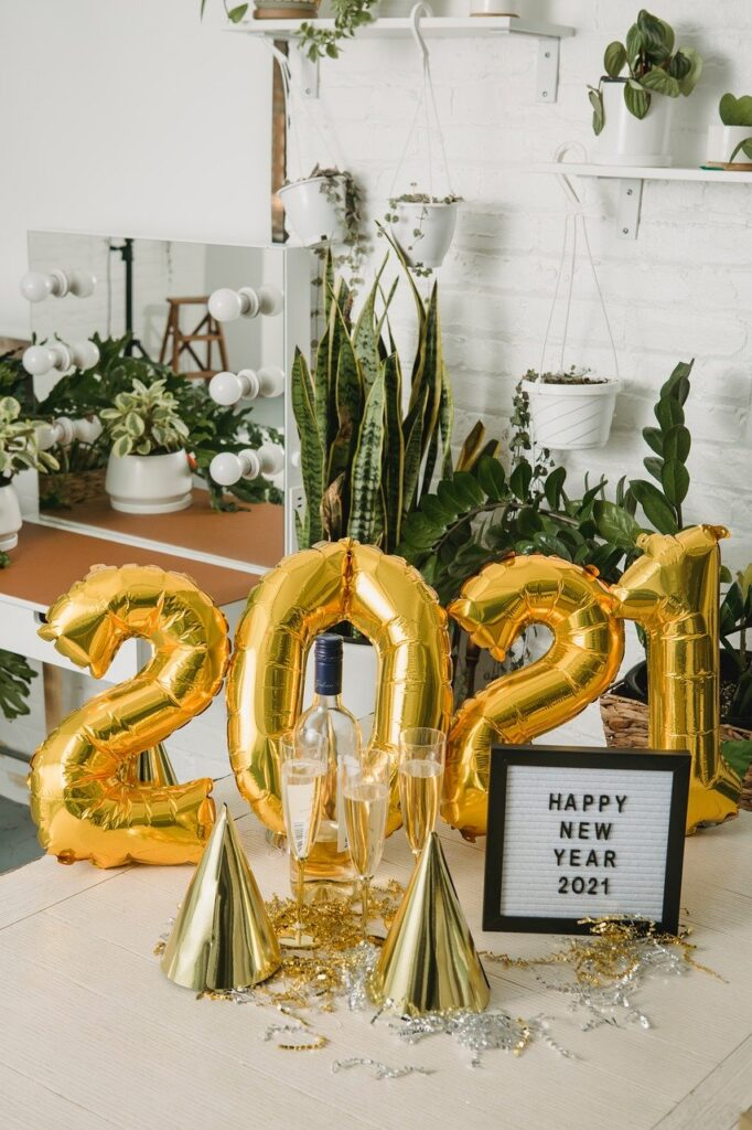 happy new year 2021 written on a frame with a ballon in gold color